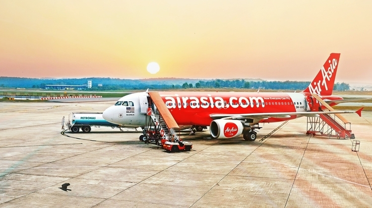 An AirAsia budget airline plane at an airport getting refueled and preparing to accept passengers in a sunset