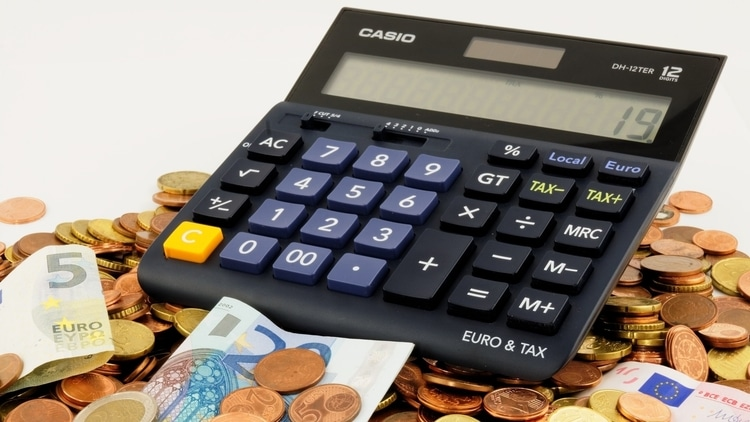 A calculator sitting on the coins and euro notes that budget travelers saved by using these top budget traveling tips