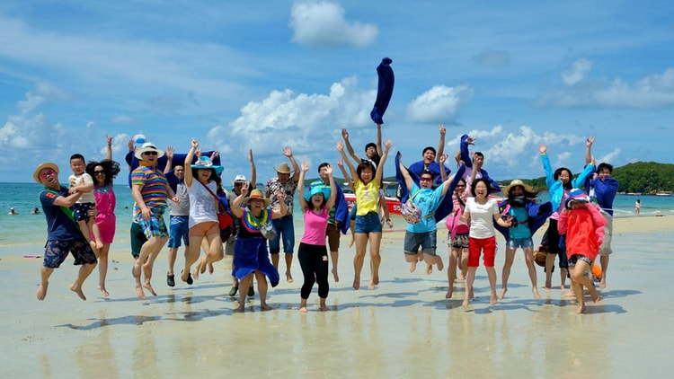 A tour group of 30 travelers jumping for joy in the air on a beach in the sun