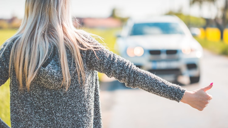 A traveler hitchhiking to get to their next destination