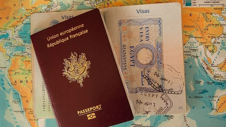 An open French traveler's passport displaying an entry visa to egypt and other stamps on top of a map of the world