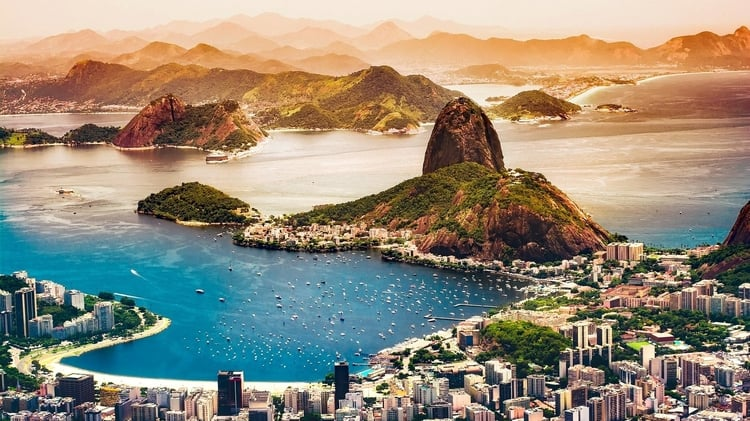 Rio de Janeiro from above with a view of the city, water, and mountains in the background