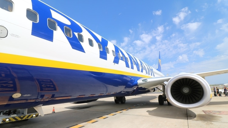 The side of a Ryanair budget airline plane parked at an airport and waiting for travelers to board