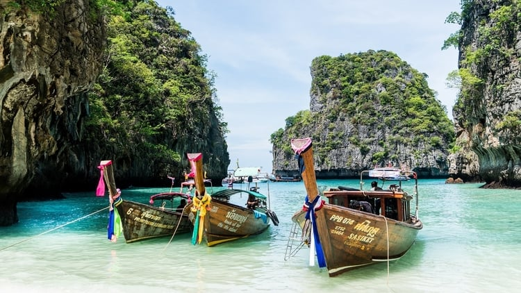Long-Tail Boats ashore in Thailand which is a top destination for budget travelers