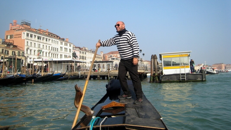 Travelers riding a gondola in venice italy driven by an italian gondolier wearing a black and white striped shirt