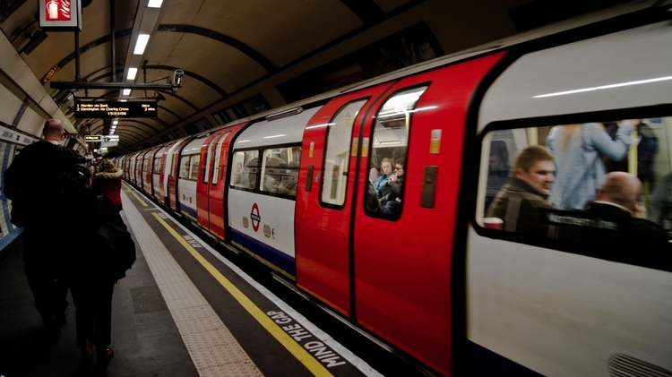 a train passing travelers in a station of the London underground