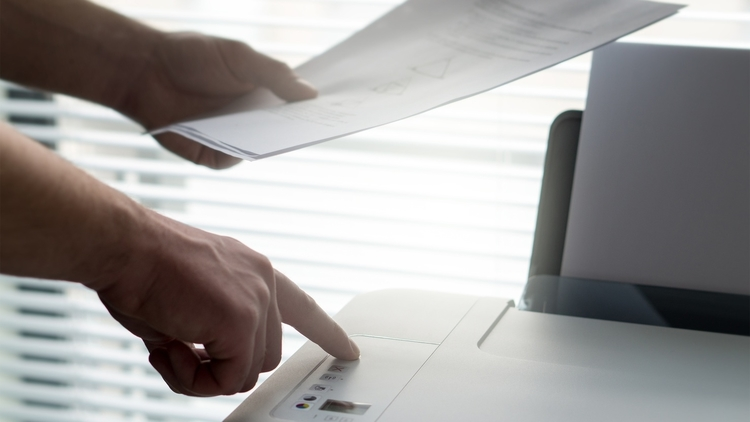 A traveler scanning and making copies of his important travel documents using a printer