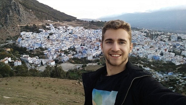 Sebastian from Travel Done Simple taking a selfie overlooking the city of Chefchaouen in Morocco