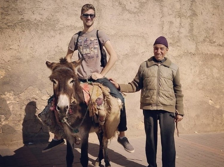 Sebastian from Travel Done Simple riding a donkey in Fez Morocco